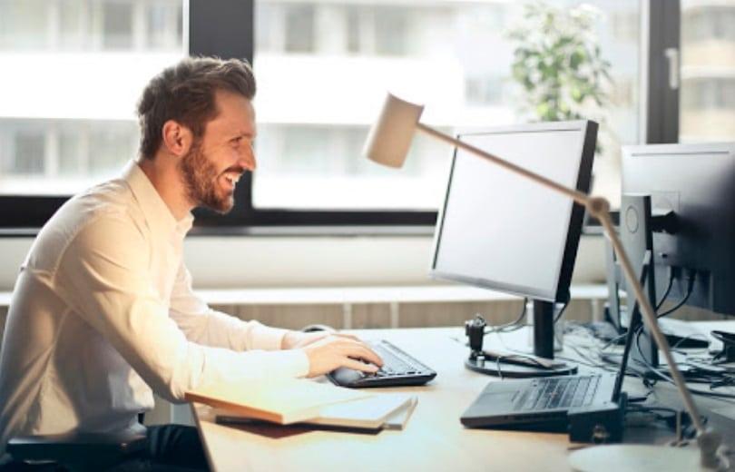 Homme souriant devant un ordinateur